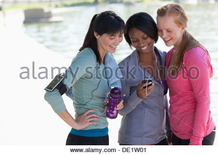 Women using cell phone together - Stock Photo