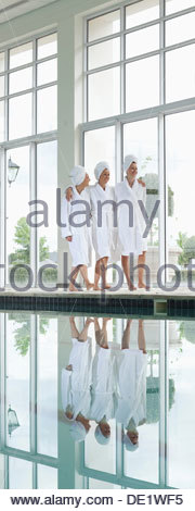 Women in bathrobes talking on bench poolside at spa - Stock Photo