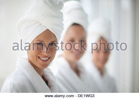 Portrait of smiling women in bathrobes and hair wrapped in towels at spa - Stock Photo