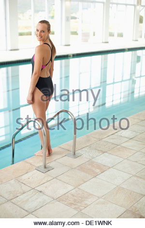 Portrait of smiling woman standing at edge of swimming pool - Stock Photo