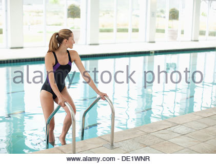 Portrait of smiling woman standing on ladder in swimming pool - Stock Photo