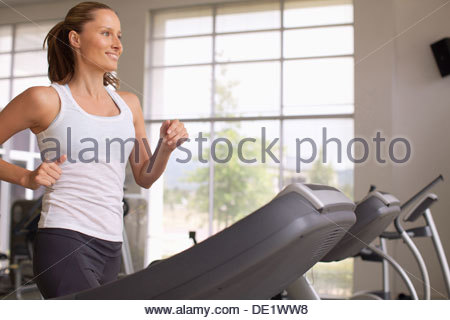 Woman running on treadmill - Stock Photo