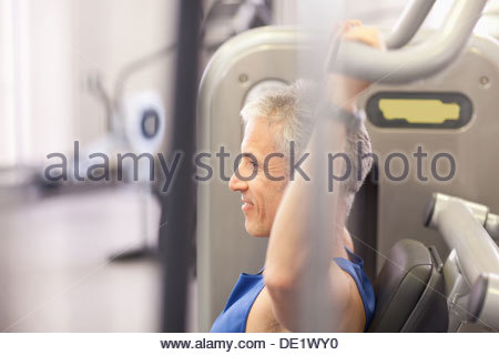 Portrait of smiling man using exercise machine in gymnasium - Stock Photo