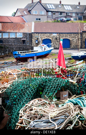 Fishing boat and nets in Craster Harbour, Northumberland, England, UK, GB - Stock Photo
