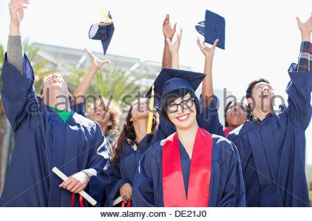 Graduates tossing caps into the air - Stock Photo