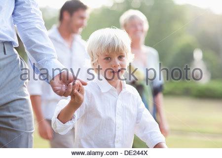 Boy walking across lawn at wedding - Stock Photo