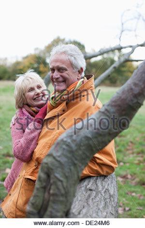 Senior couple hugging outdoors in autumn - Stock Photo