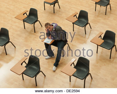 Pensive college student sitting at desk in classroom - Stock Photo