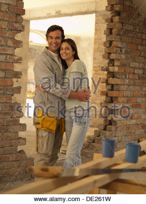 Couple hugging in doorway of house under construction - Stock Photo