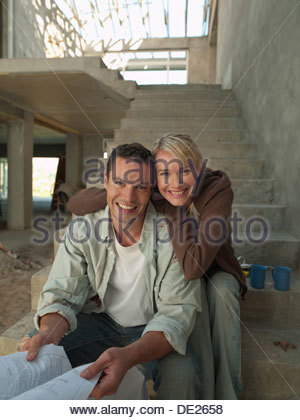 Couple looking at blueprints on staircase of house under construction - Stock Photo