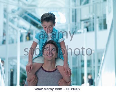 Father carrying son on shoulders in mall - Stock Photo