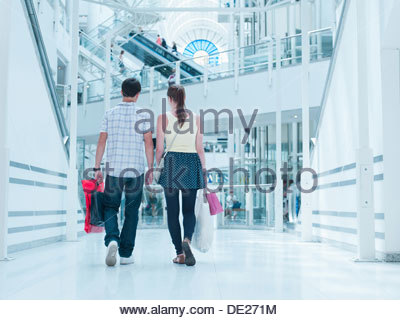 Couple carrying shopping bags in mall - Stock Photo