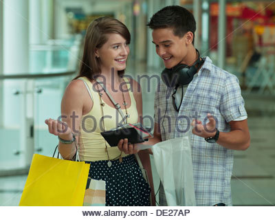 Teenage couple looking at cd rom cases in mall - Stock Photo