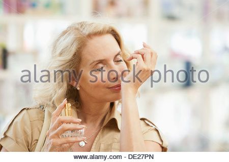 Smiling woman testing perfume in store - Stock Photo