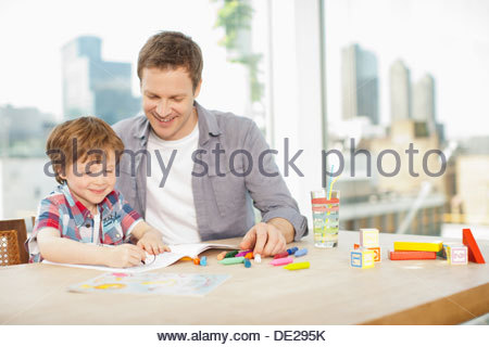 Father watching son coloring - Stock Photo
