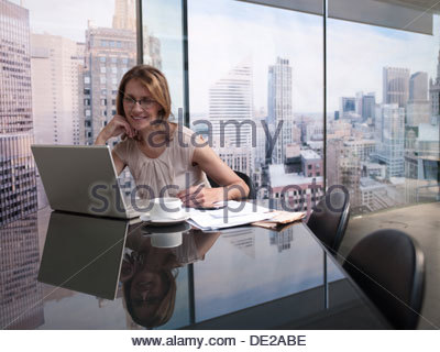 Woman working on computer with cityscape in background - Stock Photo