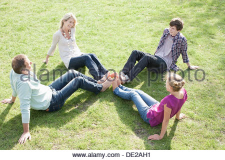 Family sitting on grass - Stock Photo