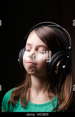 8-year-old girl with earphones listening to music - Stock Photo