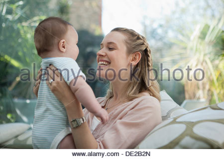 Smiling mother lifting baby son - Stock Photo