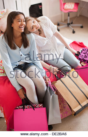 Teenage girls sitting on floor with shopping bags - Stock Photo