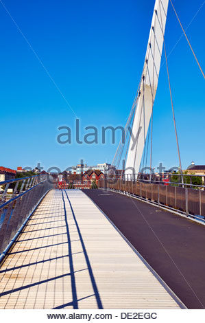 young man white top red shorts walking across sailbridge suspension bridge over river tawe in swansea marina SA1 - Stock Photo