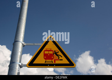 Warning sign on a station platform - Stock Photo
