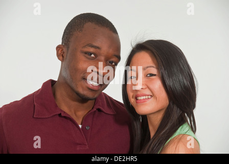 Portrait of young dark-skinned man and young Asian woman - Stock Photo