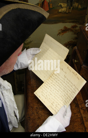 An auctioneer's assistant holds a pair of letters written by Lord Horatio Nelson in readiness for sale at a Derbyshire - Stock Photo