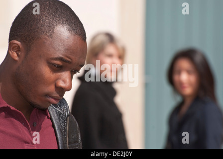 Coloured young man and two girls who are having a conversation - Stock Photo