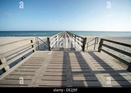 Long wooden pier, beach, blue sky and blue sea, Boltenhagen, Mecklenburg-Western Pomerania, Germany - Stock Photo