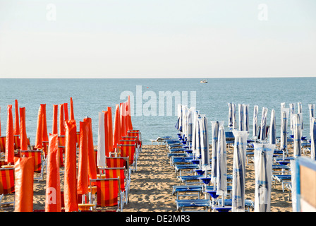 Early season, closed red and blue parasols on the sandy beach, Adria, Caorle, Venice Province, Veneto, Italy, Europe - Stock Photo