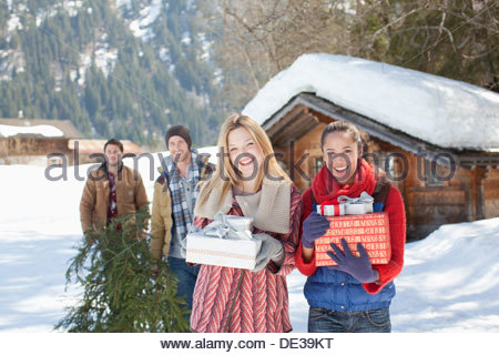 Portrait of smiling couples with fresh cut Christmas tree and gifts in snow - Stock Photo