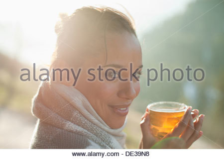 Portrait of smiling woman in scarf drinking cider - Stock Photo