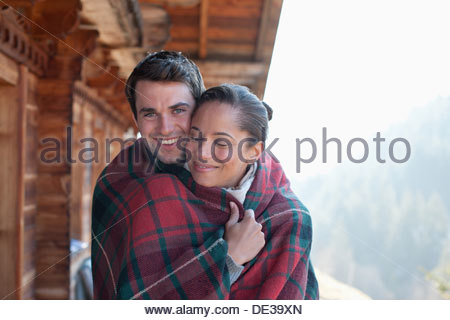 Portrait of smiling couple wrapped in a blanket on cabin porch - Stock Photo