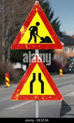 Under construction and Road narrows road signs on one pole - Stock Photo