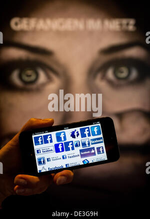 ILLUSTRATION - A man holds a smartphone displaying facebook logo in front of a placard reading 'Caught in the net' - Stock Photo