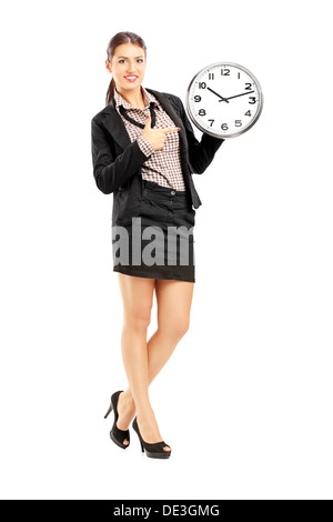 Full length portrait of a smiling female standing and pointing on a wall clock - Stock Photo
