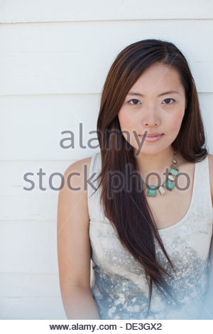 Smiling woman leaning against wall - Stock Photo