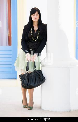 Young woman with a purse is sad - Stock Photo