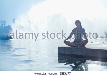 Woman meditating by still pool - Stock Photo
