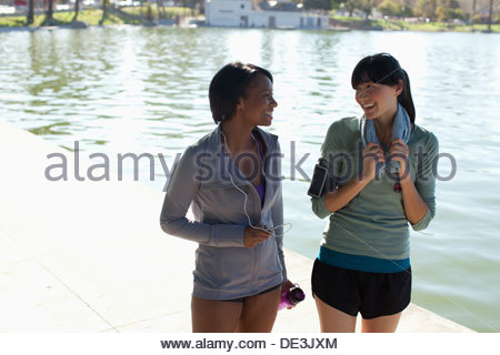 Women walking together by lake in park - Stock Photo