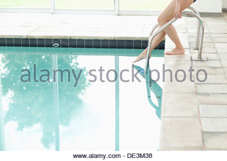 Woman dipping toe in swimming pool - Stock Photo