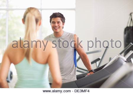 Man and woman talking on treadmills in gymnasium - Stock Photo