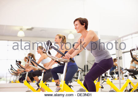 Portrait of smiling women on exercise bikes in gymnasium - Stock Photo