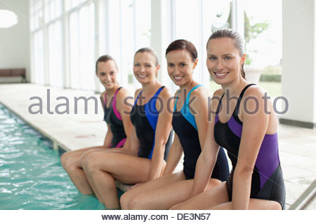 Portrait of smiling swimmers with feet in swimming pool - Stock Photo