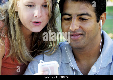 caucasion woman and ethnic man using music device together - Stock Photo
