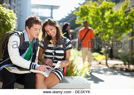 Students reading book together outdoors - Stock Photo
