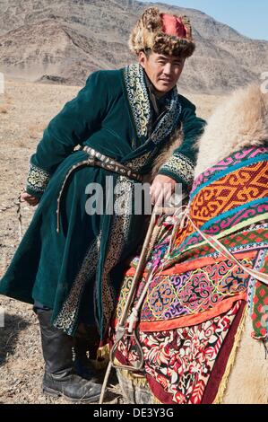 Kazakh man and his Bactrian camel on the Central Asian Steppe at the Kazakh Eagle Hunters´ Festival in the Altai - Stock Photo