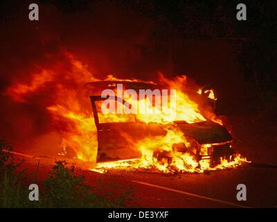 Car on fire in the street with flames blazing, Pune, Maharashtra, India - Stock Photo