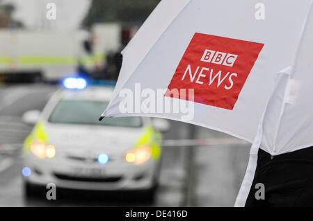 Ballyclare, Northern Ireland. 11th September 2013 -  Journalist holds a BBC News umbrella while watching police - Stock Photo